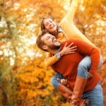 Happy couple in autumn park. Fall. Young couple having fun outdoor. Yellow trees and leaves. laughing man and woman outside. Freedom concept